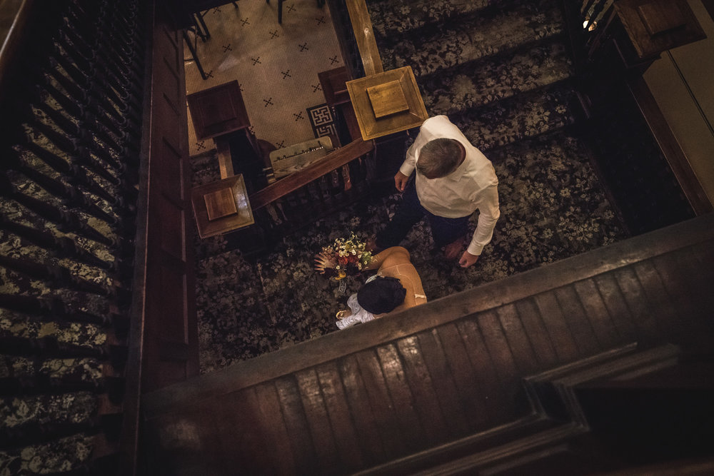 Color image of a bride and her father walking down a beautiful wooden staircase in the Hotel Boulderado.