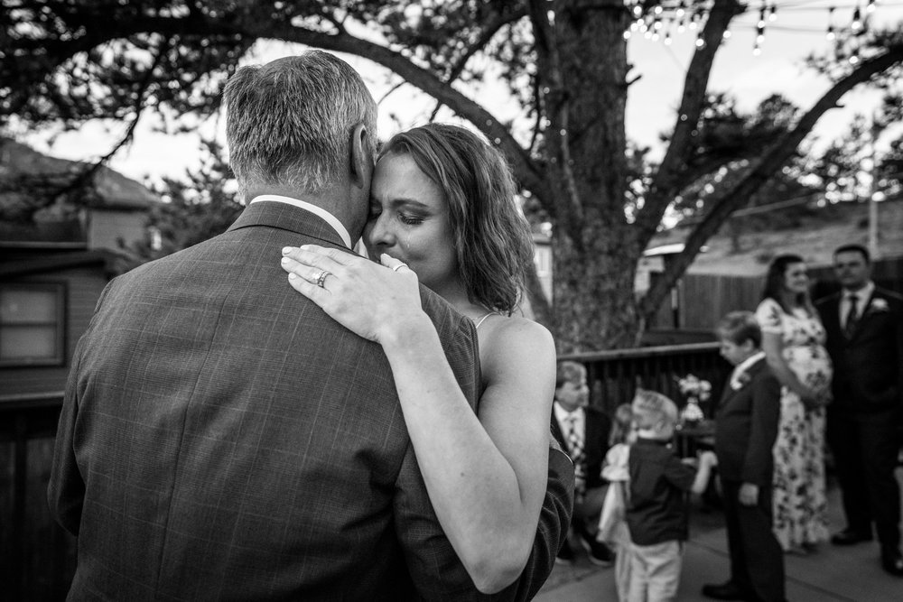 Black and white photo of a bride crying while having her first dance with her father at her wedding. Taken at the Bristlecone Inn in Estes Park, Colorado