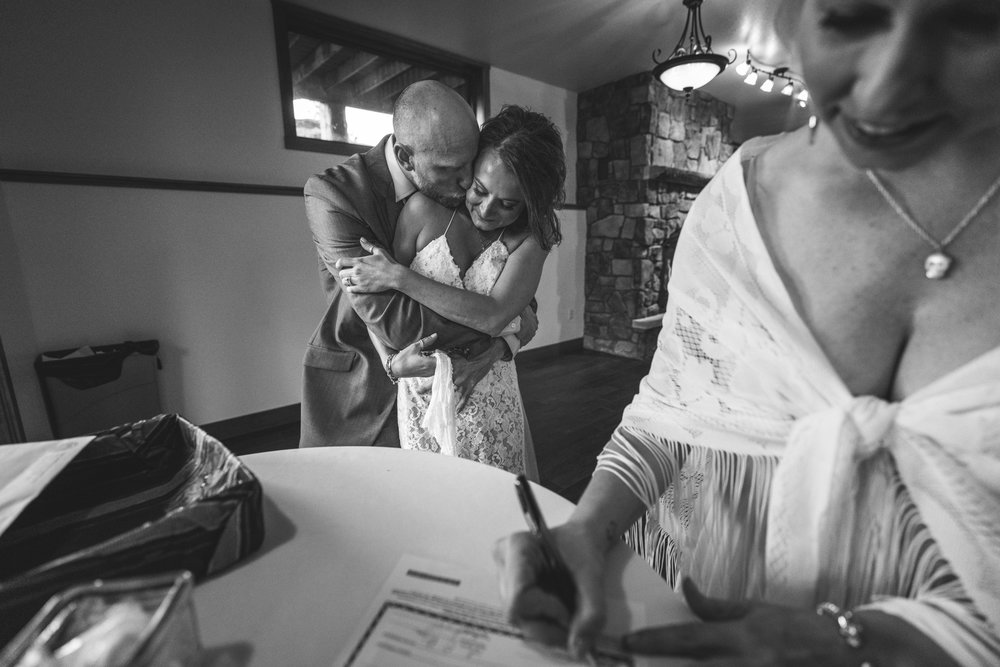 Black and white photo - a woman in the foreground signs a marriage certificate while the groom hugs his bride from the back in the background. Taken in an event room at the Black Canyon Inn in Estes Park, Colorado.