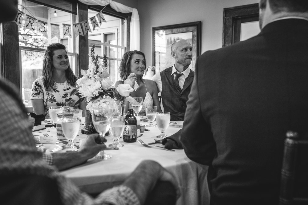 Black and white image of a bride holding a tissue while sitting at a table with her groom, crying while listening to the toasts. Taken at the Bristlecone Inn in Estes Park, CO.