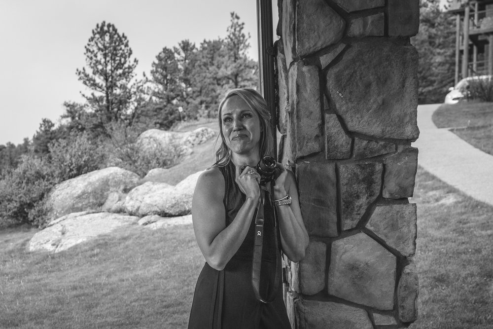 Black and white photo of a woman leaning up against a stone column with a beautiful woodsy background as she clutches a camera and cries tears of joy. Taken during a wedding ceremony in Estes Park, Colorado.