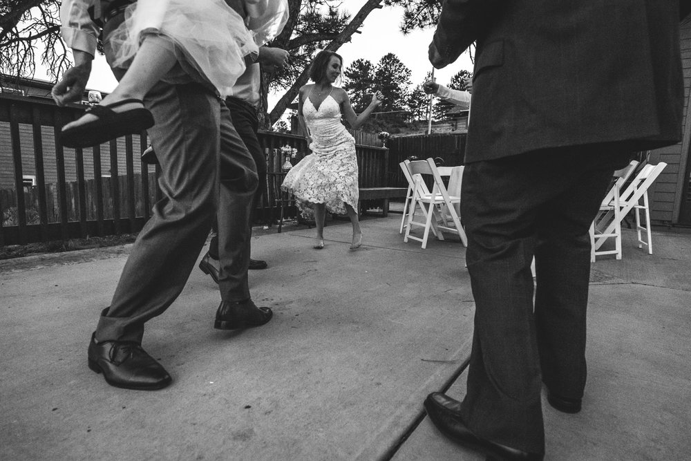 Black and white photo of a bride with her shoes off, dancing outside at her reception around several men who are wearing suits (and their shoes).