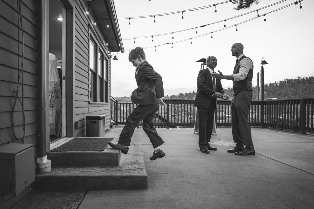 Black and white photo of a little kid at a wedding reception at the Bristlecone Inn in Estes Park, dancing on the steps outside while wearing a suit and while the groom and father-of-the-bride talk in the background.