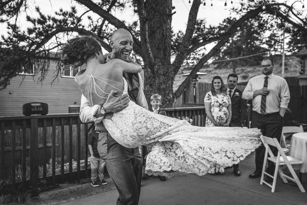 Black and white image of a groom picking up and twirling around his bride on the dance floor at their reception at the Bristlecone Inn in Estes Park, CO.