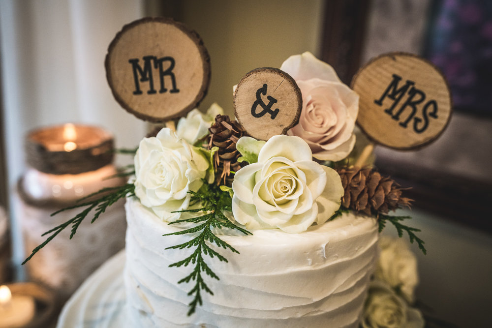 Up close wedding photo of a cake with wooden Mr. and Mrs. circles and flowers placed on top