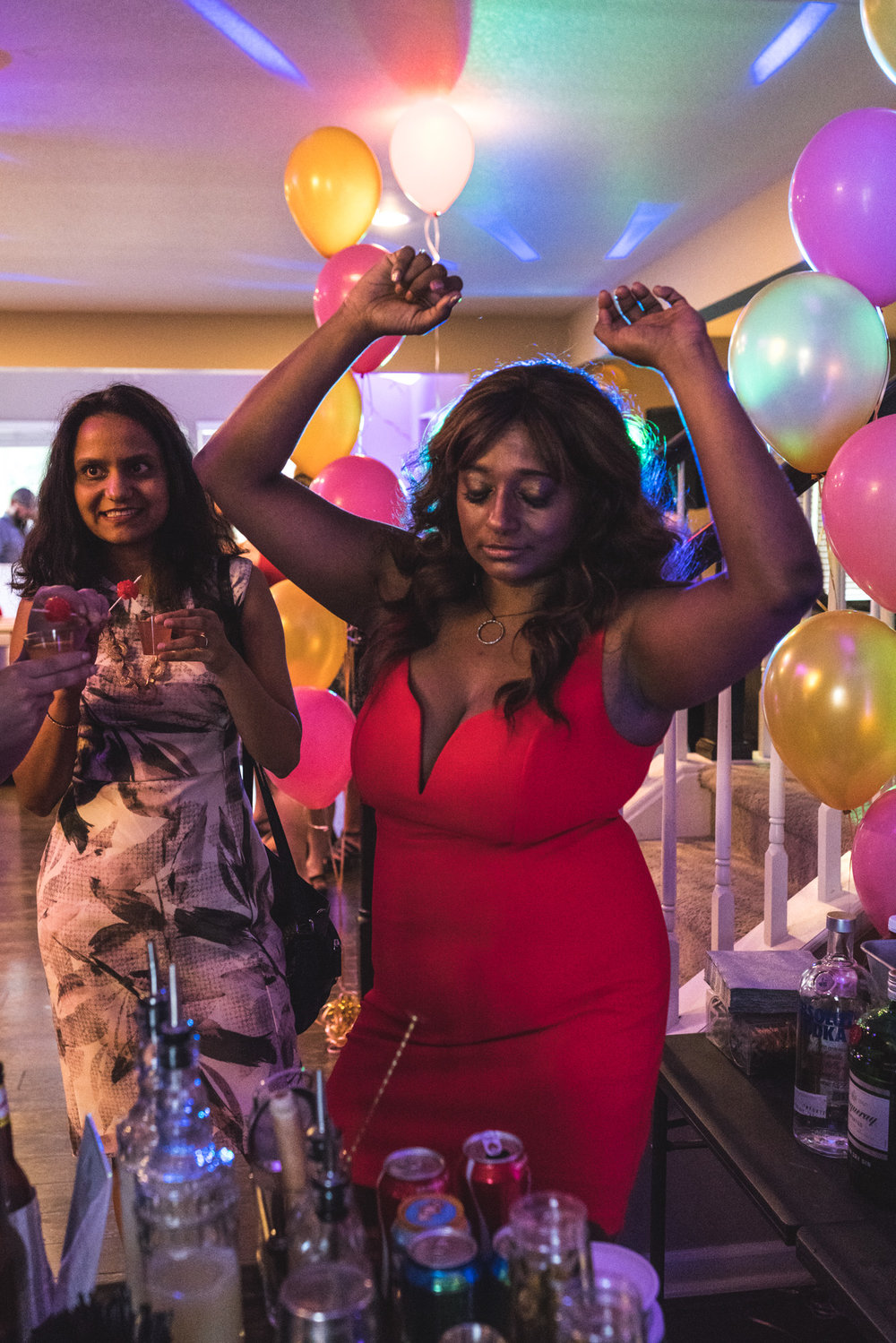Woman in a bright red dress puts her hands in the air as she dances in a room decorated with bright colored lights and balloons