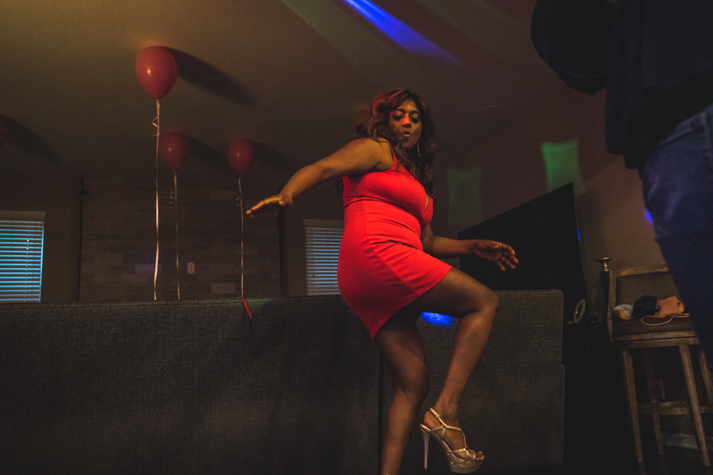 Woman in a bright red dress lifts a leg and smacks her booty as she dances at her birthday party at her home in Denver, Colorado