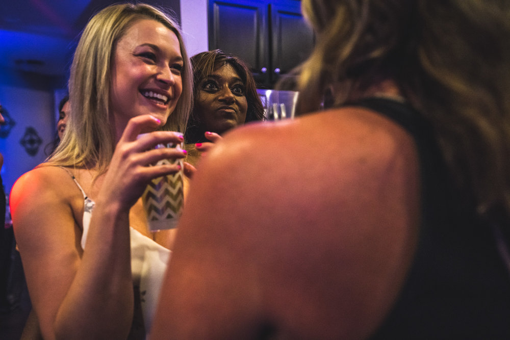 Woman peeks over one friend's shoulder to make a funny face at another friend at her birthday party