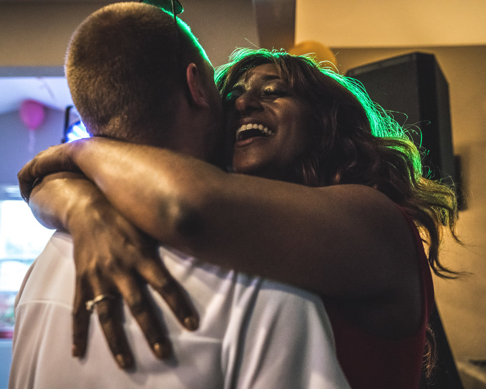Close up of woman hugging her boyfriend, smiling as her hair is haloed with green light