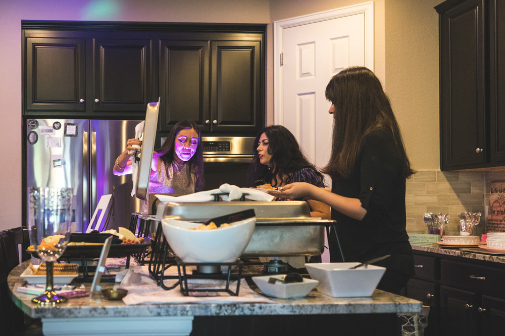 Three women look in catered dishes, one woman's face illuminated by a purple up-light.