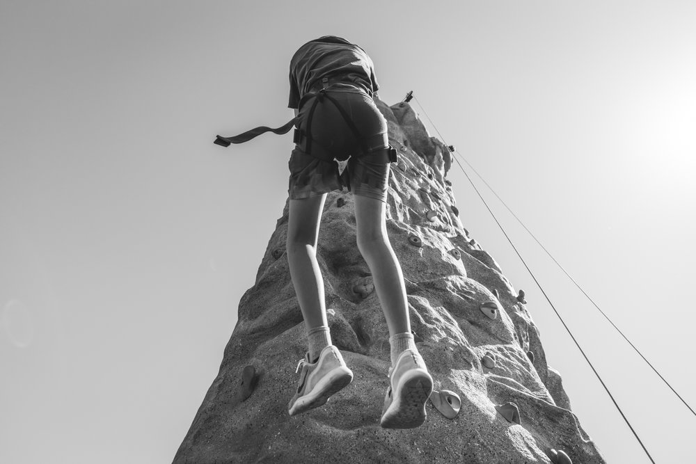 Black and white documentary event image looking up at a little boy repelling down a rock wall