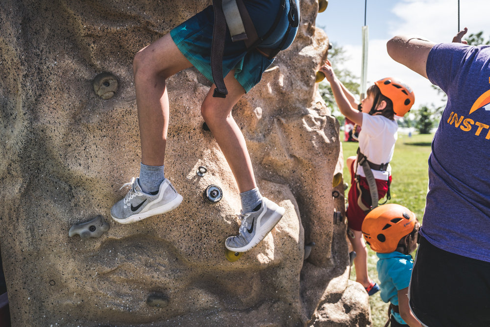 Color professional photograph of children climbing up a rock wall at a charity event in Denver, Colorado