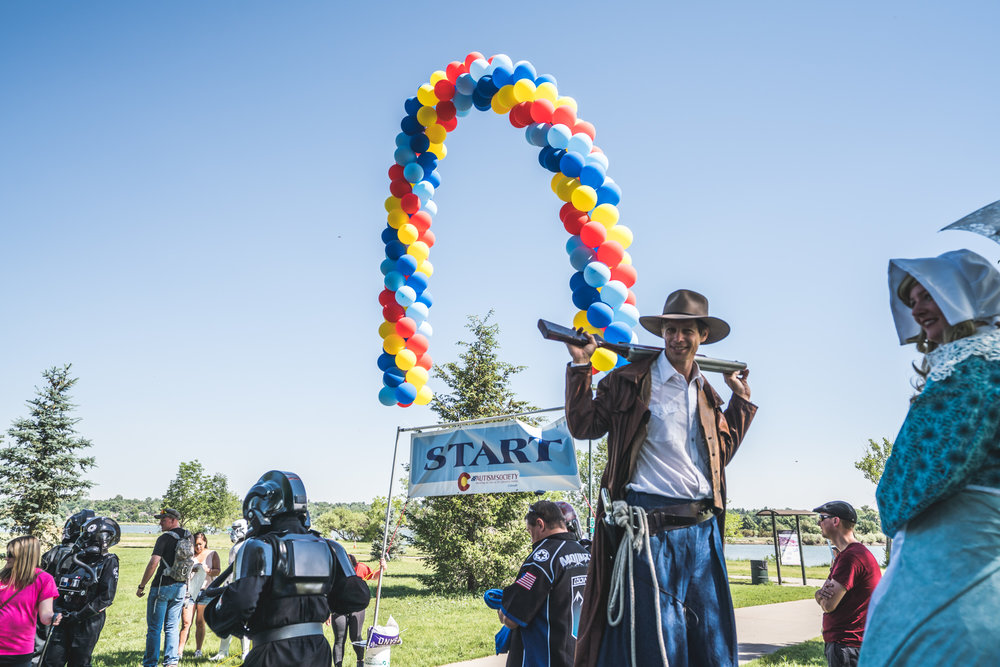 People gathered at Sloan Lake at the starting line of the Autism Society of Colorado Walk With Autism event, including a pioneer couple on stilts and sci-fi characters