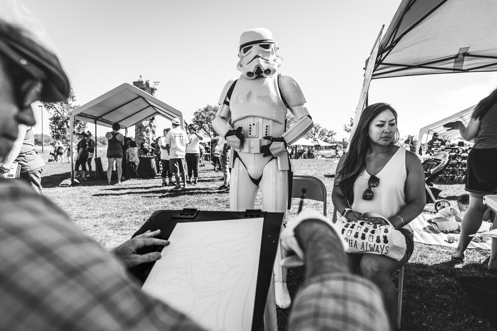 Black and white image at an outdoor charity event of a storm trooper getting drawn by a caricaturist