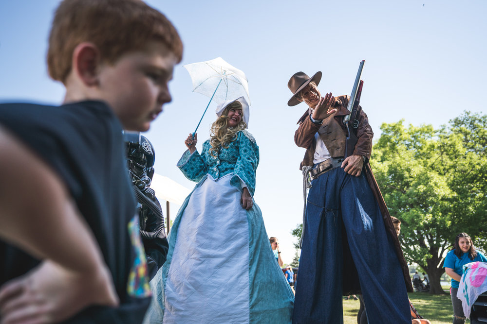 Stilt walkers dressed as pioneers wave at the kids at an outdoor event
