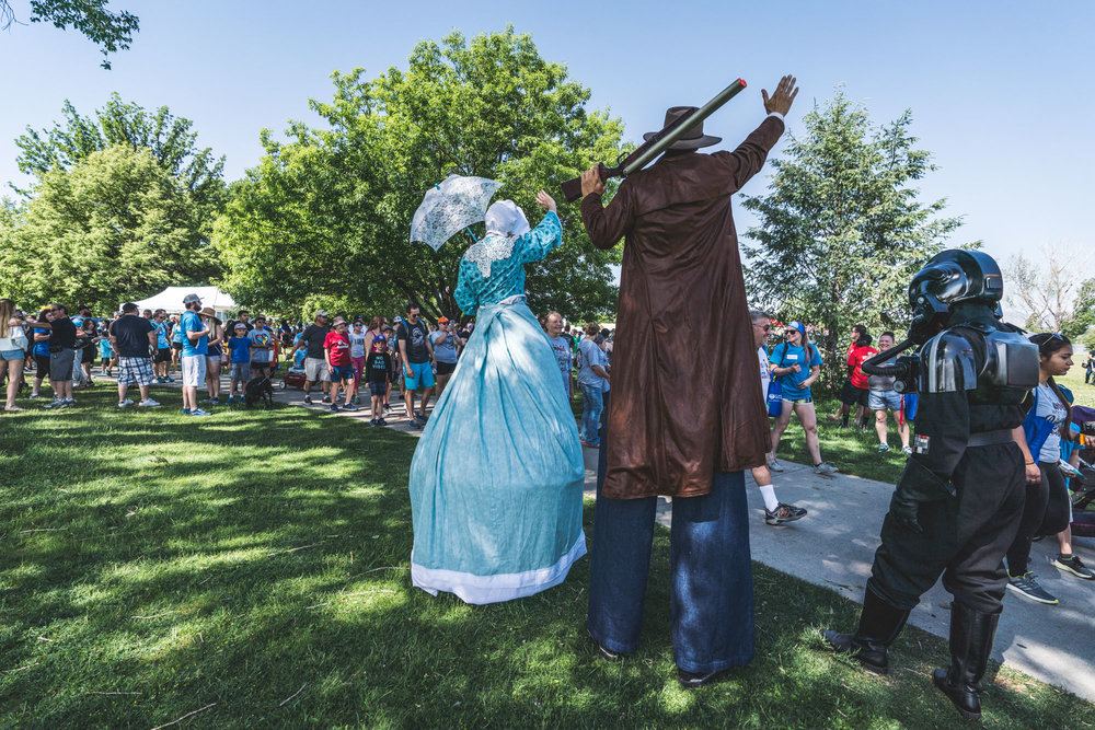 Characters on stilts wave to the individuals participating in the Walk With Autism fundraising event at Sloan's Lake in Denver