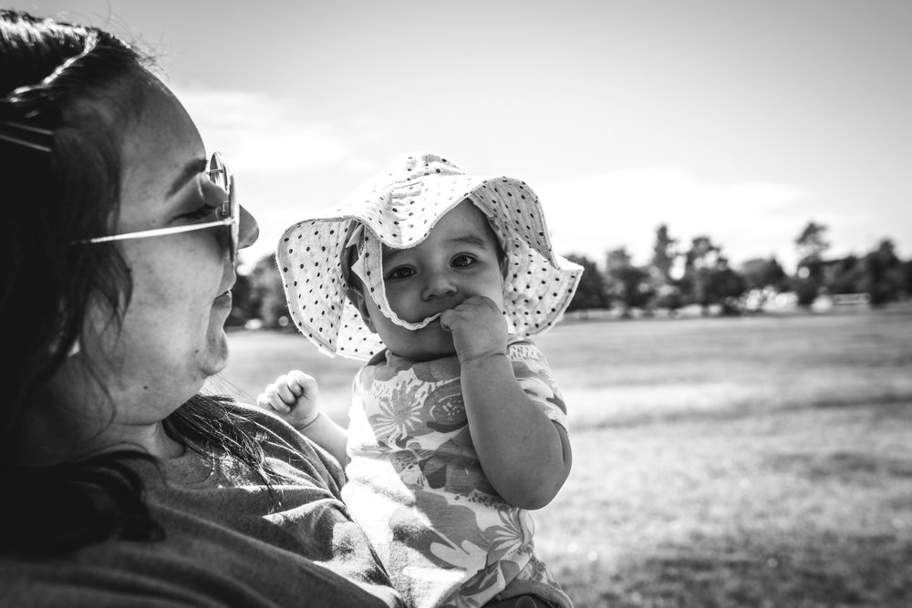 black and white image of a mother on a walk while holding her sweet baby girl who is wearind a white polka dotted hat
