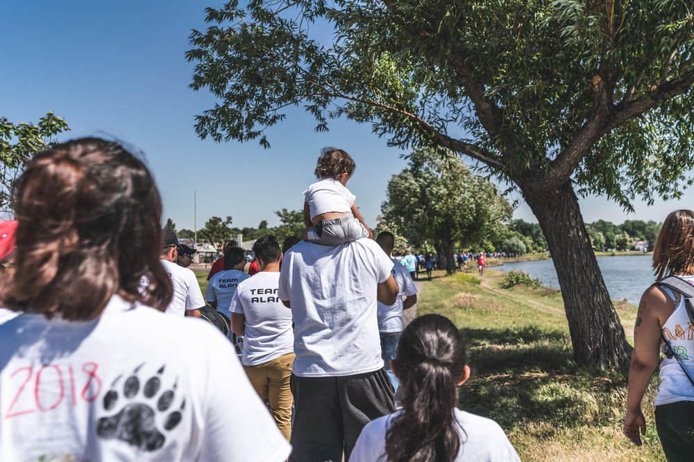 Group walks around Sloan's Lake in Denver for the Autism Society's Walk with Autism event, a little girl on her father's shoulders