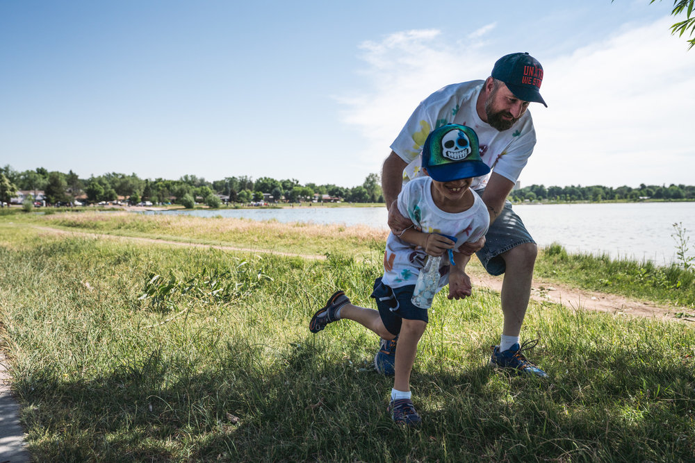 Father and son play chase at Sloan's Lake in Denver, CO