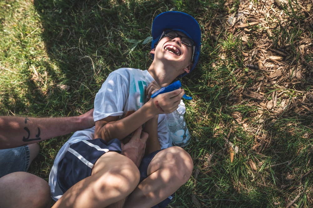 Little boy lying in the grass laughing while his father tickles him