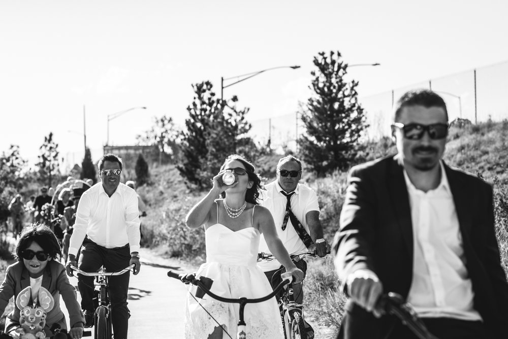 Black and white photo of a bride, groom, and their guests riding on bikes, the bride taking a swig of her beer