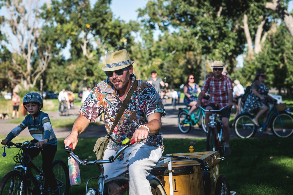 Colorful photo of a man wearing a hat riding a bike with a lot of people on bikes surrounding him