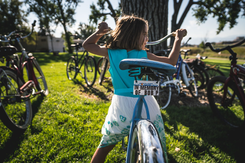 """Little girl sits on a bike, surrounded by other bikes. The back of her bike bears a license plate that reads """"In Memory of Bob P."""" The little girl is wearing a fancy dress."""