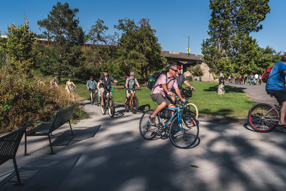 Group of people dressed for a wedding ride bikes around Berkeley Lake in Denver, Colorado