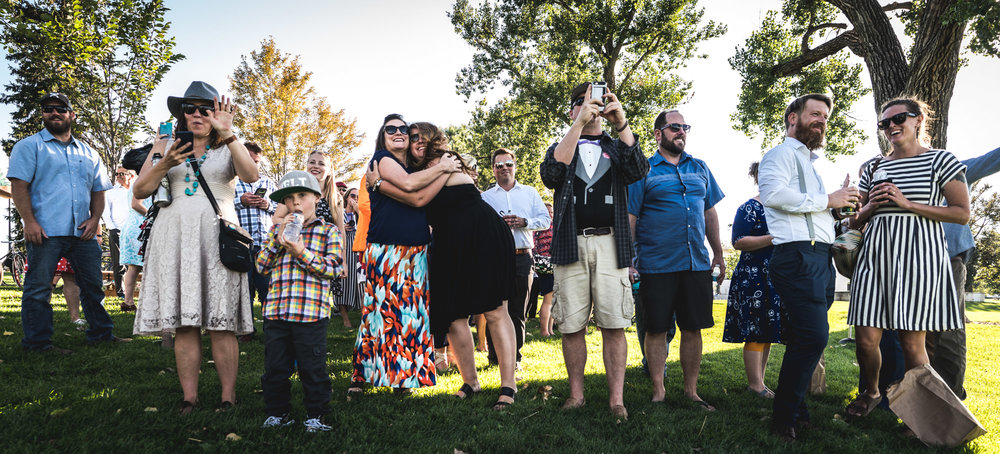 Wide shot of a bunch of wedding guests outdoors amongst trees smiling, hugging, and laughing