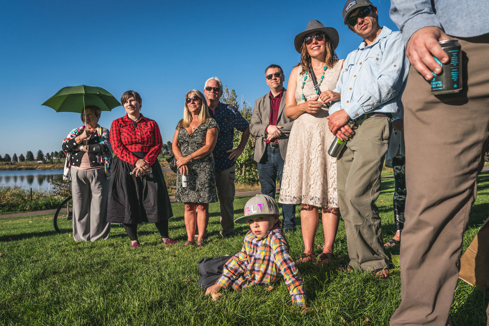 Guests at an outdoor wedding in Denver, Colorado wearing colorful formal wear watch the ceremony