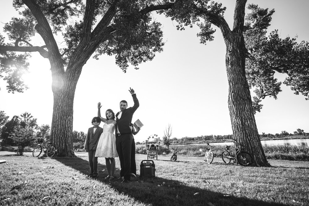 Newlyweds and groom's son stand under a tree, arms up in celebration