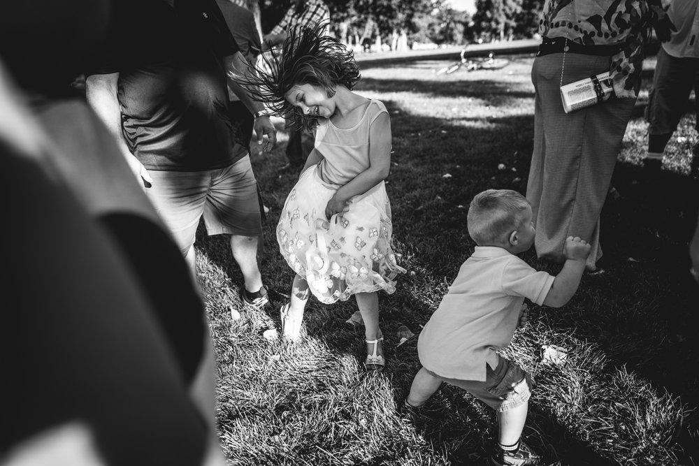 Little kids dancing in formal wear at an outside wedding in Berkeley Park in Denver, CO