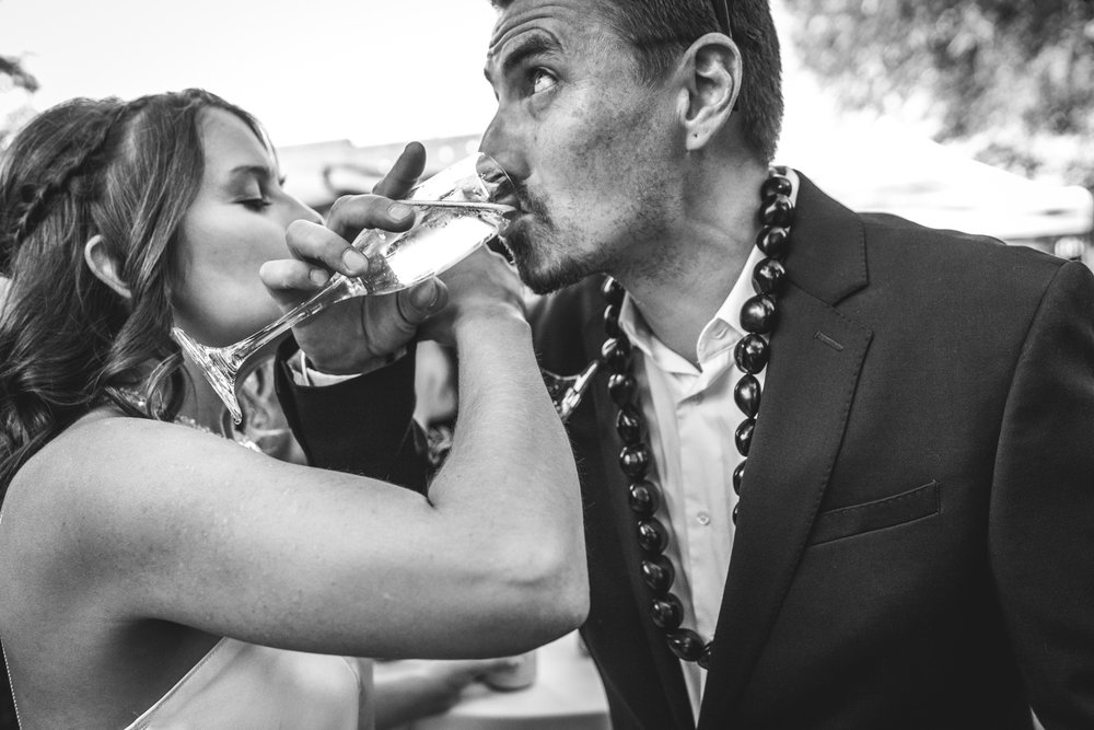 Bride and groom lock arms and take a drink of champagne at their reception