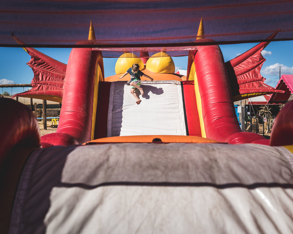 Little boy jumps down a giant bouncy house slide at a pumpkin patch in Parker, Colorado