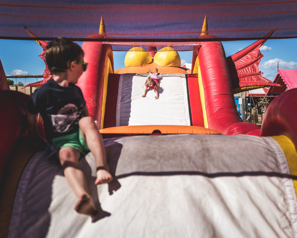 Girl slides down a bouncy house slide while her brother watches