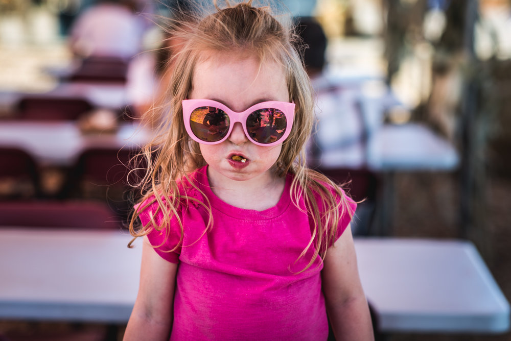 Little girl wearing pink glasses and a pink shirt looks straight to camera with a gigantic bite of food in her mouth.