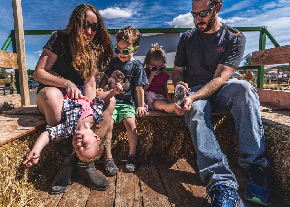 Parents and their three kids play around on the hay ride at a pumpkin patch in Parker, Colorado