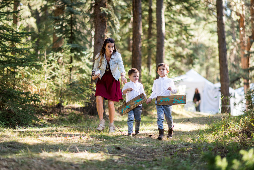 "Two kids run down the aisle in the woods with ""Here comes"" and ""your bride"" signs while their mother attempts to wrangle them in."