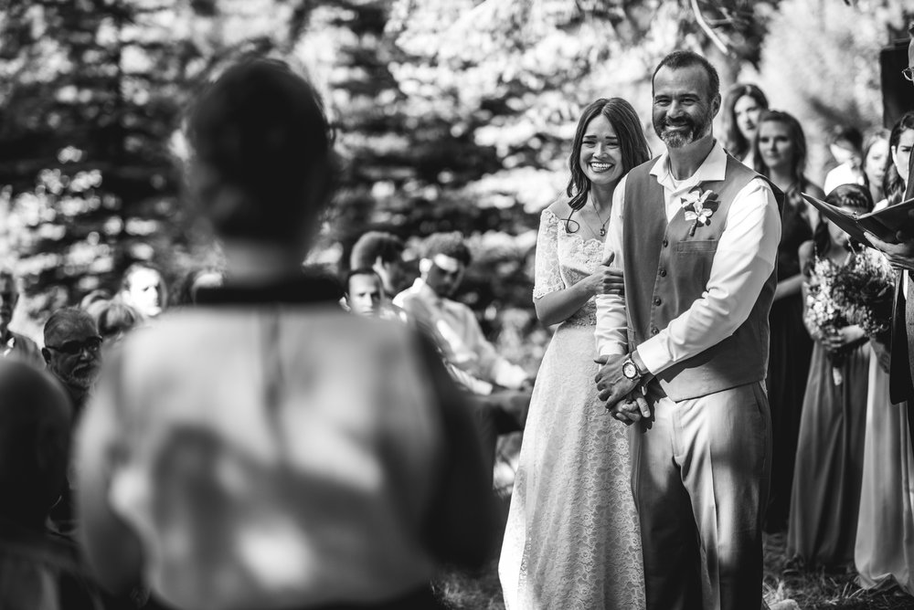 Bride and groom smile wide as a family friend reads a speech during their wedding ceremony