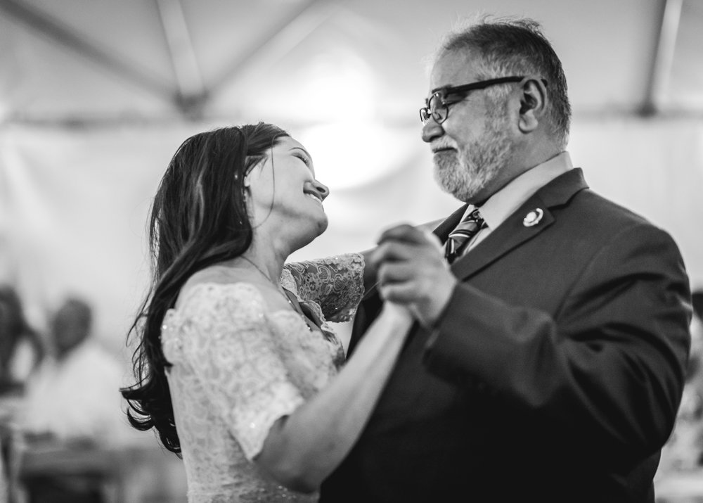 Bride and her father smile as they dance at her wedding reception