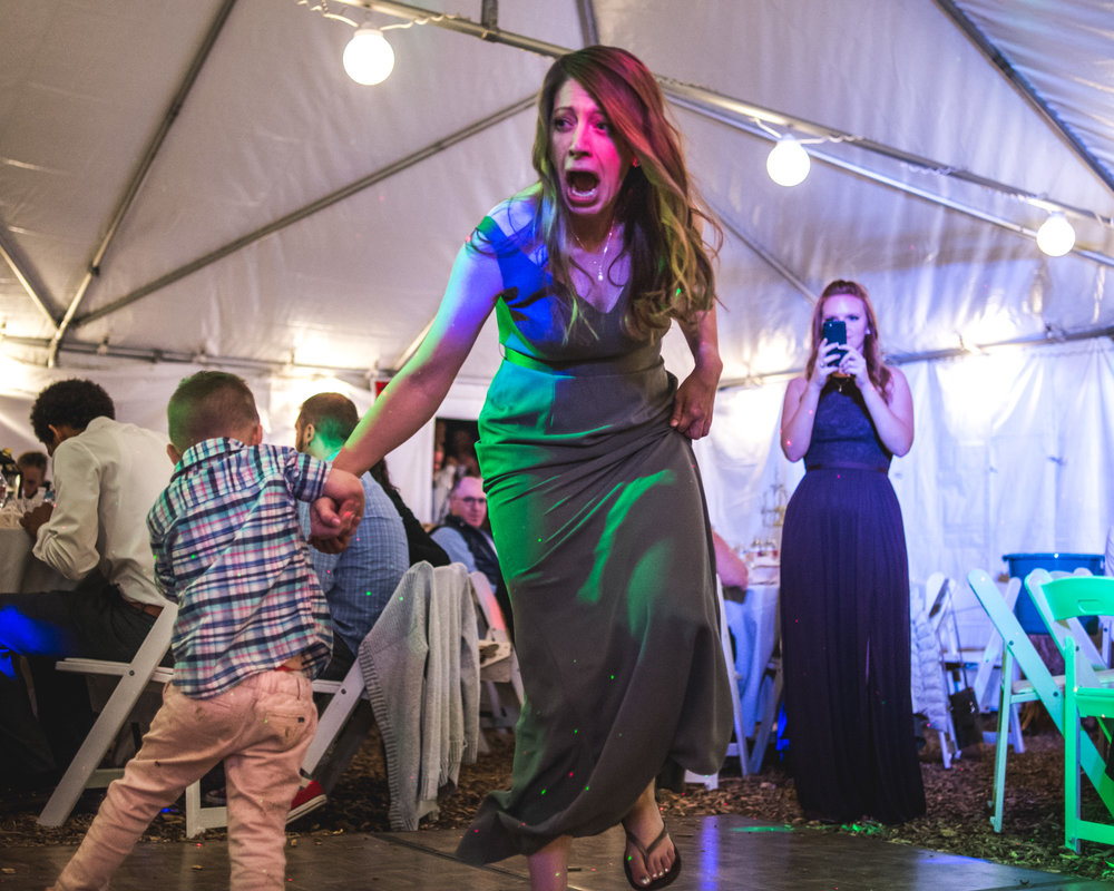 Bridesmaid at a wedding in Morrison, Colorado screams as a young kid twirls her crazily on the dance floor