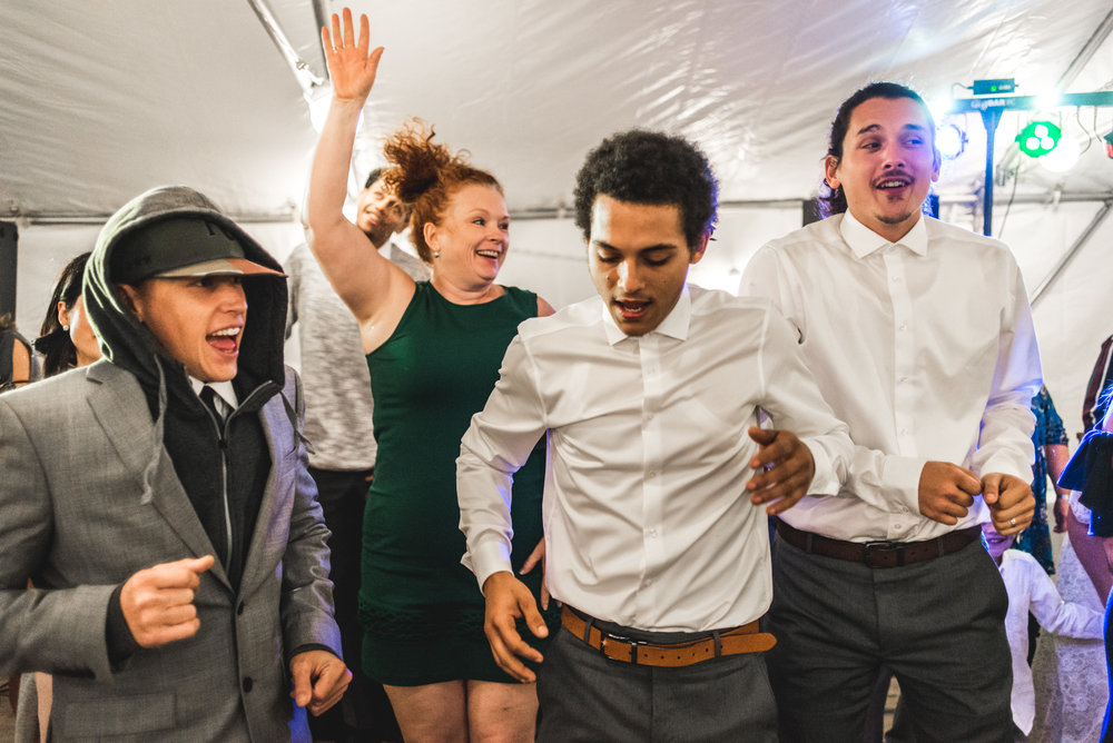 Group of people jump as they dance at a wedding reception in Colorado