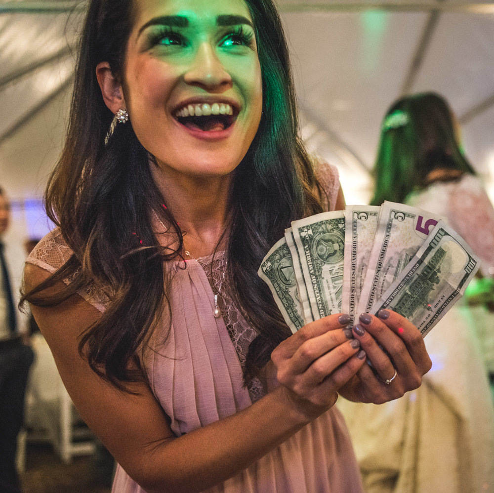 Bridesmaid at a wedding reception holds up cash made from the dollar dance