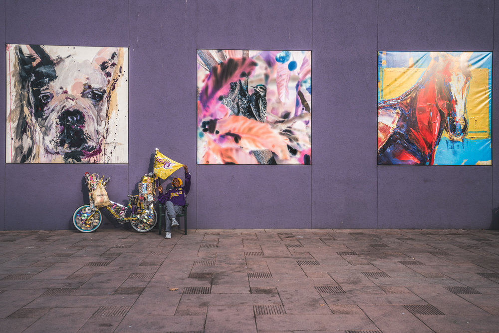 Woman sitting between paintings in Pershing Square holds up an LA Lakers flag