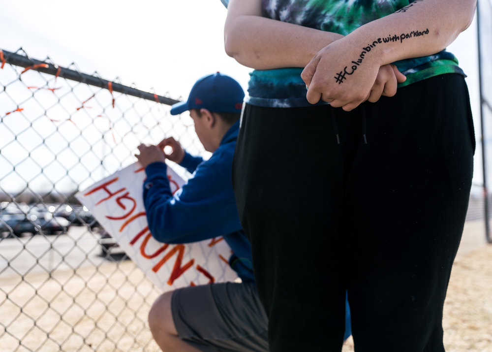 Close up photo of a woman with #Columbineforparkland written on her arm at the Columbine student walkout