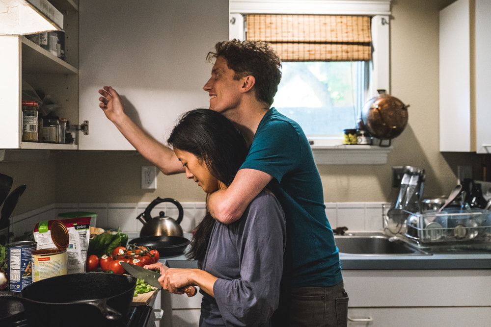 Husband wraps an arm around his wife, who is cooking, while he looks in the kitchen cabinet