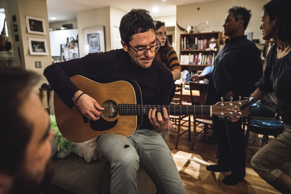 A man at a house party makes a funny face as he strums an acoustic guitar