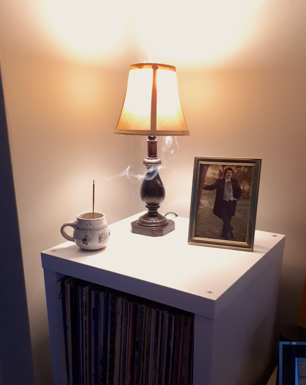 Our small lamp on top of the records shelf helps reflect light against the ceiling, creating a glow in the room. The use of a yellow-tinted shade helps diffuse warmer light into the room. And lights up a super cool picture of my Dad during his wedding day in the 80's! That perm!