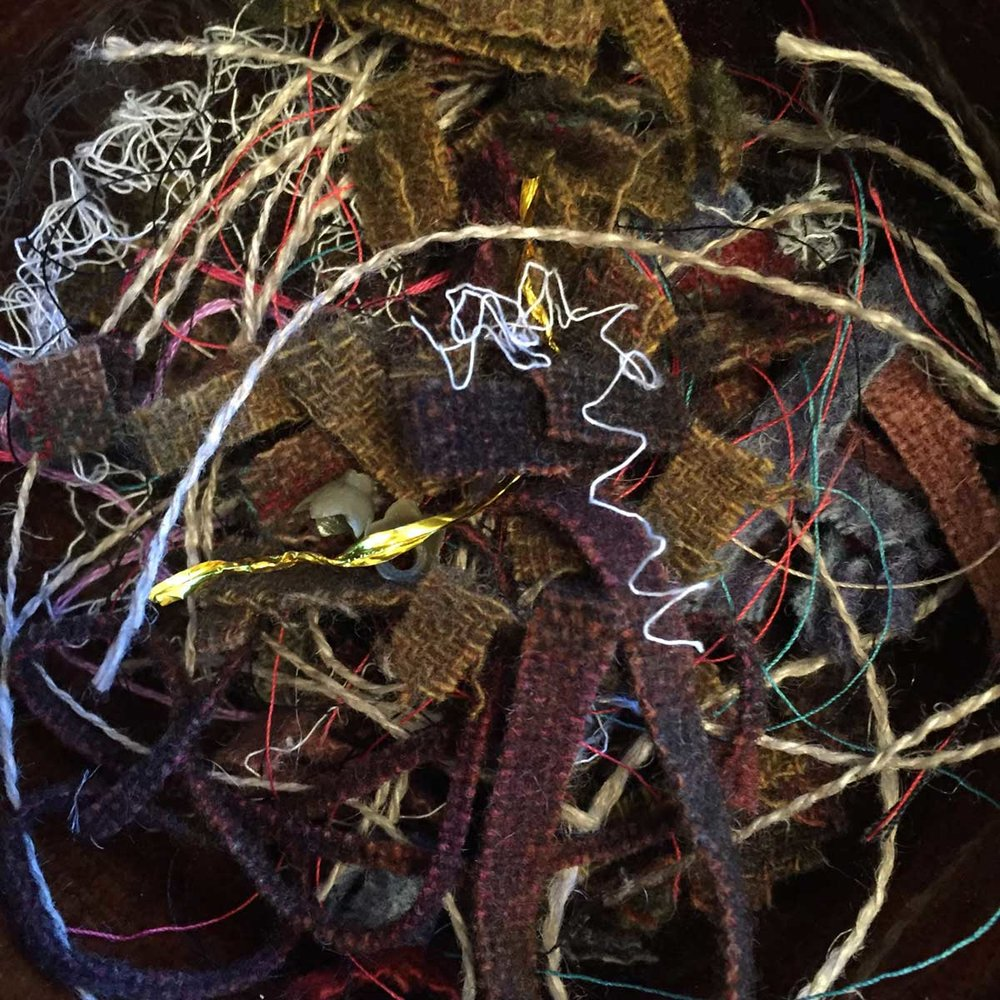 Colorful threads and bits of wool strips from making a  hooked rug