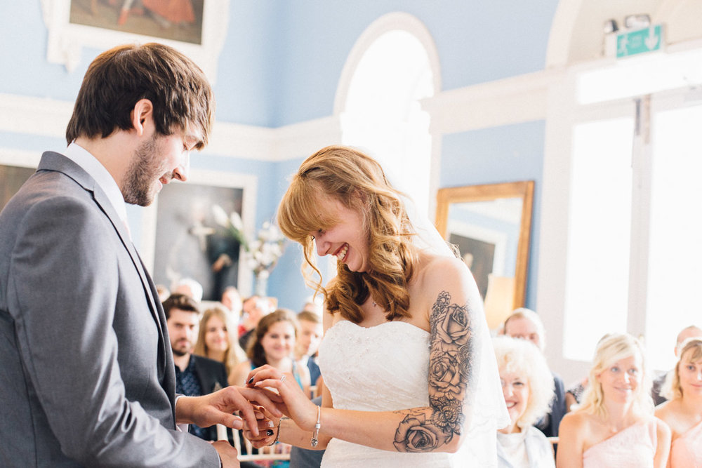 Bride Laughing Whilst putting Ring on Grooms Finger